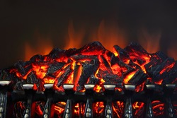 Glowing coals and fire flames in fireplace with metal grating