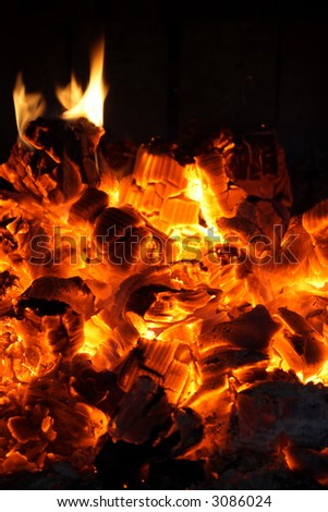 Glowing coals and fire flames in the fireplace.