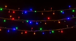 glowing colorful Christmas lights on black background