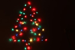 Glowing colourful christmas lights on dark isolated background