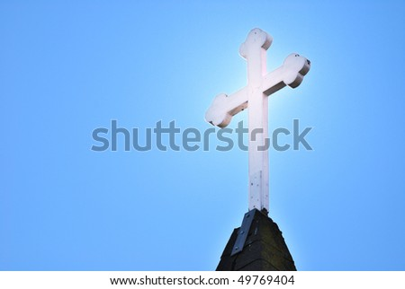 Glowing cross atop a steeple against a blue sky