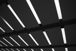 Glowing daylight lamps on ceiling in darkness. Abstract minimal architecture, interior and technology background photo with geometric structure of parallel lines on black.