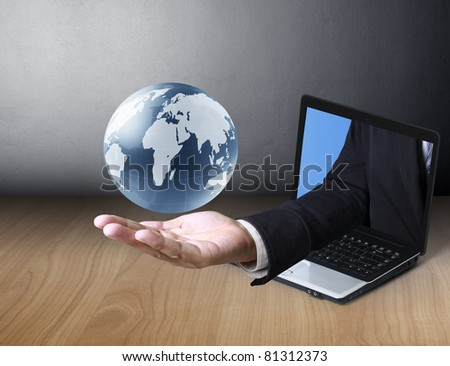 glowing earth globe in his hands, and a laptop