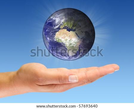 Glowing Earth on open palm