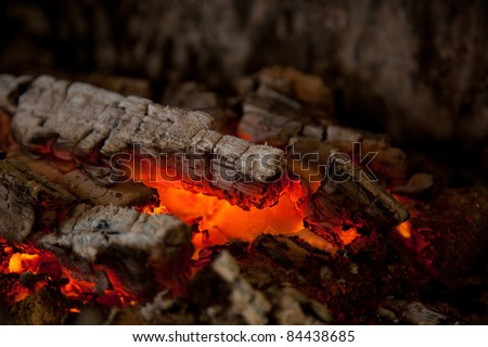 Glowing embers from burned down fire in fireplace