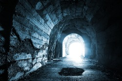 Glowing exit from dark abandoned tunnel. Monochrome blue photo