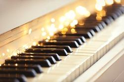 Glowing fairy lights on piano keys, closeup. Christmas music