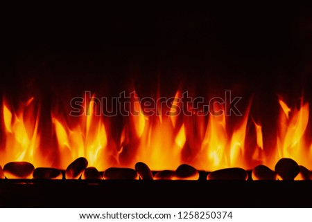 Glowing fire in the stone fireplace #1258250374