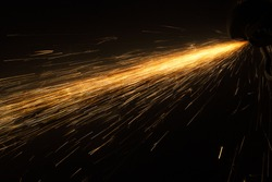 Glowing flow of steel or metal grinding spark particles shine in the dark background