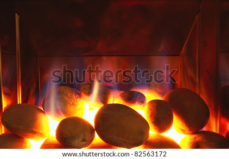 Glowing gas fire with flames. Stones glow white hot in this fireplace.