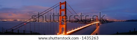 Glowing Golden Gate bridge on a stormy evening in winter. Blue dusk with departing storm clouds contrast with the San Francisco skyline lit by thousands of lights. Traffic flows as two-colored river.