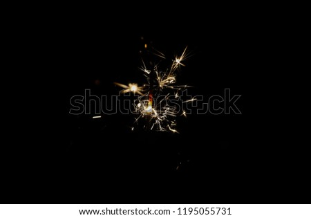 Glowing golden sparkler in the dark, abstract background, Christmas joy, sparkling Bengal light, copy space for your text