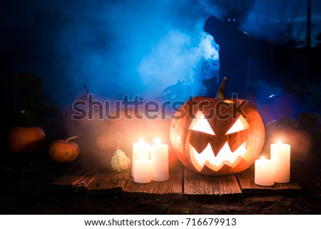 Glowing Halloween pumpkin with scarecrows on the field #716679913