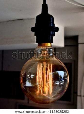 Glowing hot filament of tungsten in Edison Light Bulb, glowing dim in daylight being used for interior decoration.