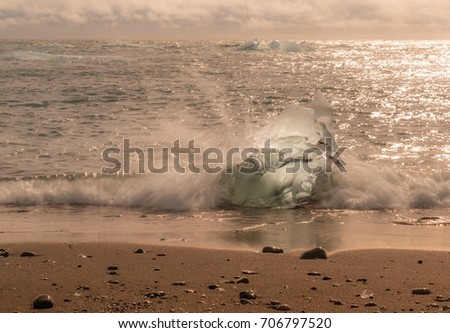 Glowing hunk of ice on beach in Iceland with surf spray #706797520
