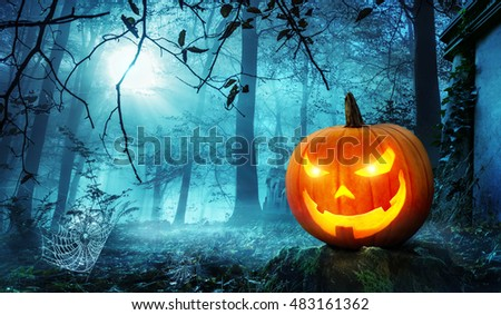 Glowing Jack o lantern in a creepy old overgrown cemetery with cool blue moonlight #483161362