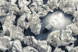 Glowing light bulb among the crumpled rubbish paper, idea from mistake concept