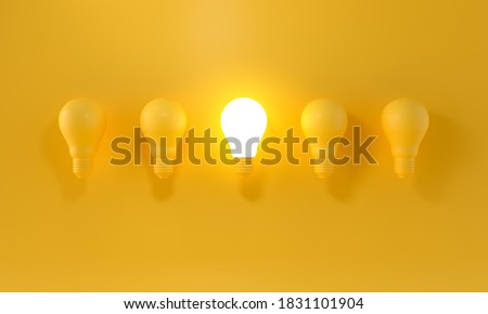 Glowing Light Bulb between the others on yellow light background. Leadership, innovation, great idea and individuality concepts. 3d rendering. Foto d'archivio ©