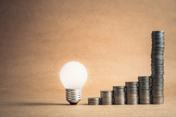 Glowing light bulb with heap coins stair that sudden steep higher progress in the last step, high earnings or success in the long term for finance and business concept
