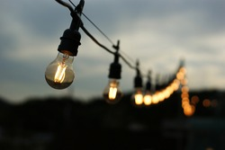 Glowing light bulbs hang in a row in the darkened sky.