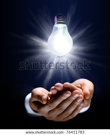 Glowing lightbulb and hand