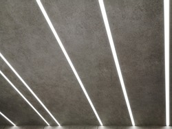 Glowing lines of modern daylight lamps on ceiling or wall with texture resembling asphalt. Abstract minimal architecture, interior or technology background photo with geometric linear structure.