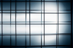 Glowing matte glass panels of wall or ceiling in shades of blue color. Abstract modern architecture background in minimalism style. Geometric pattern of parallel lines and cellular graphic structure.