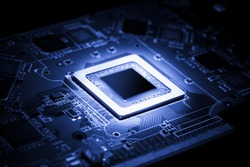 Glowing modern processor. Big illuminated graphic processor surrounding by other electrical components. Special tone image. Low aperture shot, focus on lower part of chip.