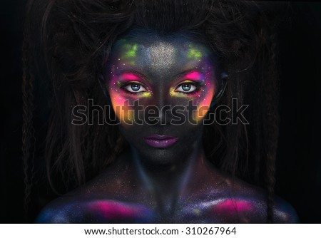 Glowing neon makeup with dramatic look in his eyes. ?reative body art on the theme of space and stars.