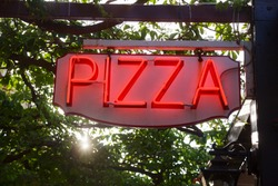 Glowing neon Pizza sign at a pizzeria
