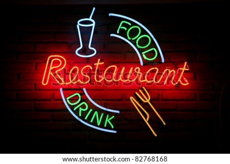 Glowing neon sign on brick wall saying restaurant food drink
