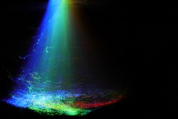 Glowing optical fibers forming the effect of a waterfall on a black background. Light painting technique.