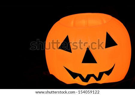Glowing orange pumpkin/Halloween Smile/Orange pumpkin with face on a black backgrounf