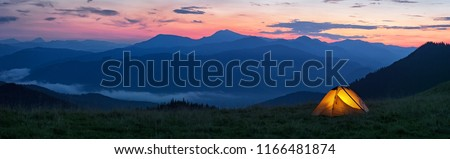 Glowing orange tent in the mountains under dramatic evening sky. Red sunset and mountains in the background. Summer landscape. Panorama