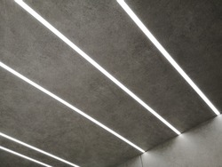 Glowing parallel lines of modern daylight lamps on ceiling or wall with texture resembling asphalt. Abstract minimal architecture, interior or technology background photo with geometric structure.