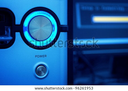 glowing power button of computer and blurred monitor on backdrop