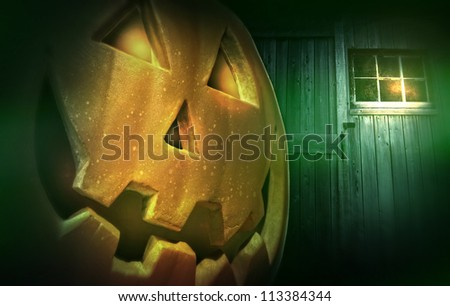 Glowing pumpkin at night in front of barn door