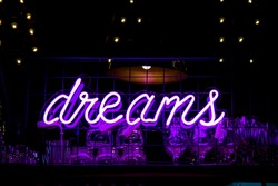 Glowing Purple Neon Inscription DREAMS and glasses on blurred lights background. Dark tones vintage image.