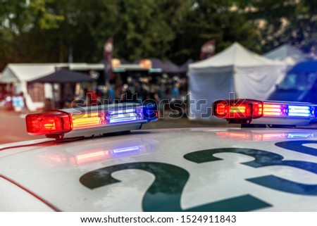 Glowing red-blue flashing lights on the roof of a police car #1524911843