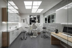Glowing room in a dental clinic with light walls and dark gray floor. There is a workplace with a dental chair and equipment, table with a computer, zone with a sink, mirror, window, glass partition.