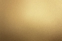 Glowing rough bronze metal board wall, abstract texture background