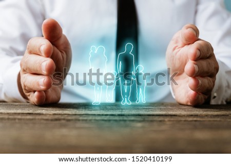 Glowing silhouette of a family on virtual interface with male hands making protective gesture around it in a conceptual image.