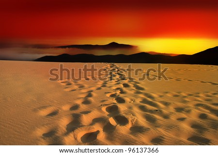 Glowing sundown in the desert with footsteps in the sand