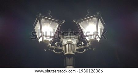 Glowing triple classic street lamp in the black night sky, with pink and blue reflections on the sides (bottom view). Foto stock ©