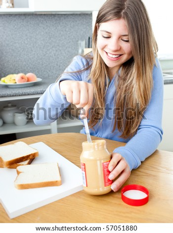 Glowing woman woman eating peanut butter in a kitchen