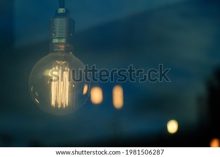 glowing yellow tesla decorative glass light bulb in the dark, stylish electrical Edison hanging lamp for interior art spotlight illumination and decoration, retro design home decor detail, idea symbol