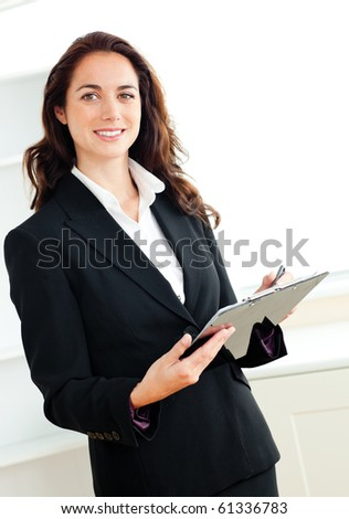 Glowing young businesswoman taking notes on her clipboard against a white background