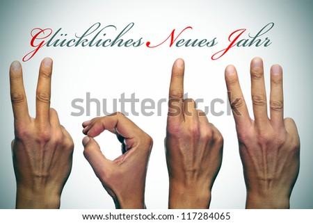 gluckliches neues jahr, happy new year written in german, with hands forming number 2013