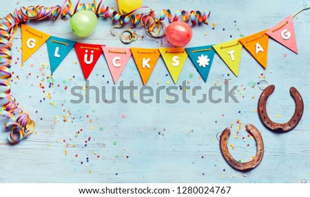 Glucks Tag or Good Luck background with copy space and a border of festive colorful flags, streamers, balloons and two symbolic horseshoes #1280024767