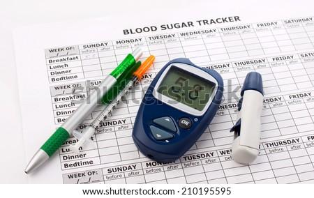 glucometer, diabetes syringe, pen and medical form on white background